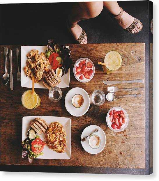 Overhead View Of Woman's Legs And Breakfast Table Canvas Print by Justhanni