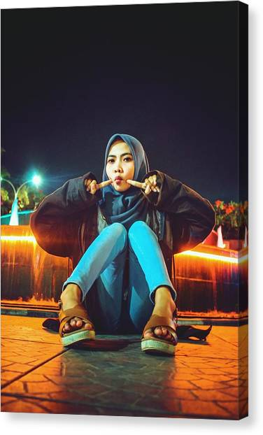 Portrait Of Young Woman Wearing Hijab While Sitting On Footpath At Night Canvas Print by Ilham Adhi Kusuma / EyeEm