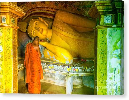 praying buddhist monk by a lying buddha in Sri Lanka Canvas Print by Gina Koch