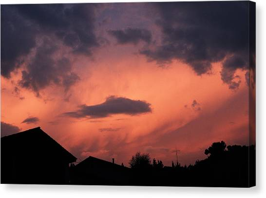 Purple Clouds Gather In A Pink Sky Above Dark Houses Canvas Print by Photodisc