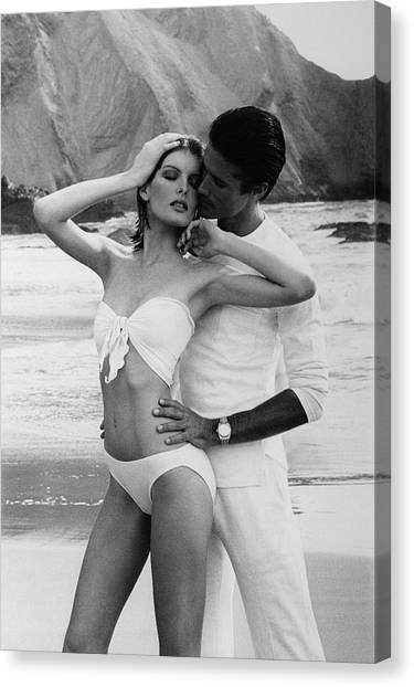 Rene Russo Posing With A Male Model On A Beach Canvas Print by Francesco Scavullo