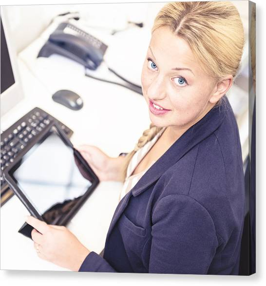 Secretary In Her Office Using A Digital Tablet Canvas Print by Franckreporter