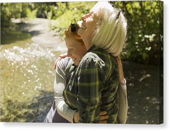 Senior Woman And Daughter Hiking Hugging By River Canvas Print by Compassionate Eye Foundation/Steven Errico