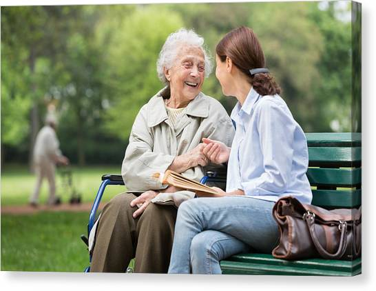 Senior Woman With Caregiver In The Park Canvas Print by FredFroese