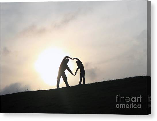 Silhouette Couple Forming A Heart Canvas Print by Lars Ruecker
