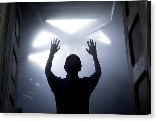Silhouette Of A Man With Raised Hands Against Light Coming From Above. Canvas Print by Maciej Toporowicz, NYC