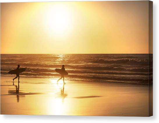 Canvas Print featuring the photograph Silhouette Of A Surfers At Sunset by Georgi Djadjarov
