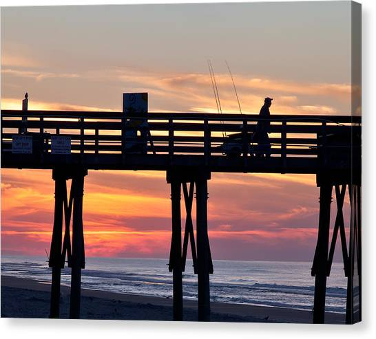 Silhouetted Fisherman On Ocean Pier At Sunrise Canvas Print