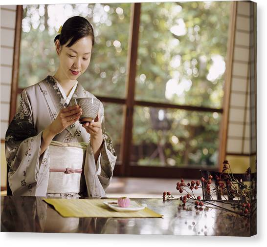 Smiling Woman Drinking Tea During A Japanese Tea Ceremony Canvas Print by Digital Vision.