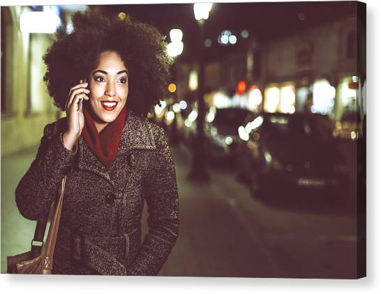Smiling Young Woman Using Phone On Street By Night Canvas Print by Portishead1
