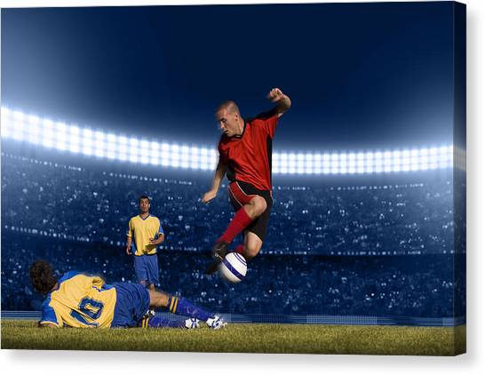 Soccer Player Jumping With Ball Canvas Print by Kycstudio