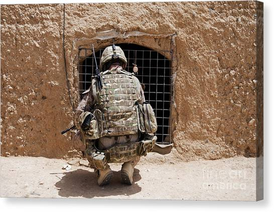Nato Canvas Print - Soldier Searches A Compound by Stocktrek Images