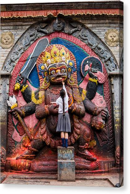 Kali Canvas Print - A Nepali School Girl Offers A Butter Lamp To The Fearsome Kala Bhairava by Nila Newsom