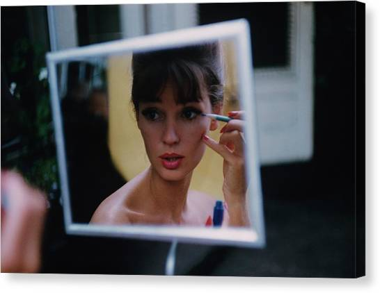 The Reflection Of A Model Applying Make-up Canvas Print by Karen Radkai