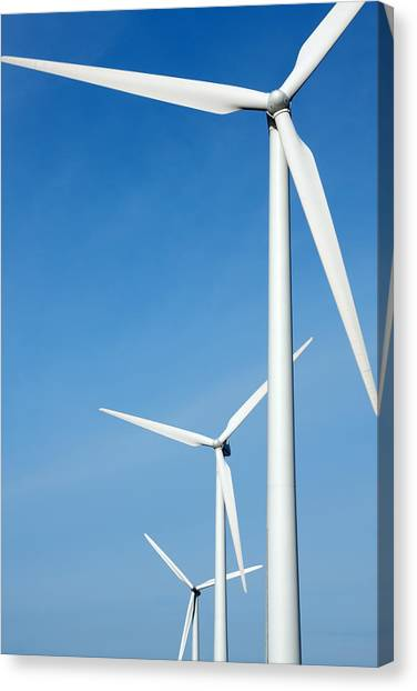Three Mighty Windmills In A Row Against A Blue Sky. Canvas Print