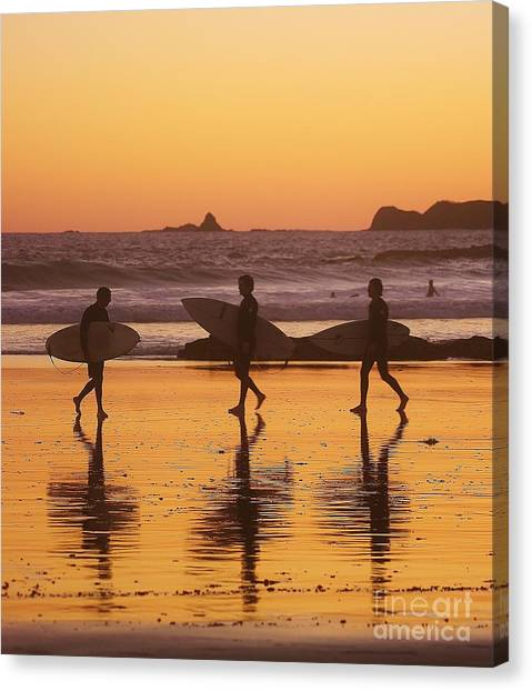 Three Surfers At Sunset Canvas Print