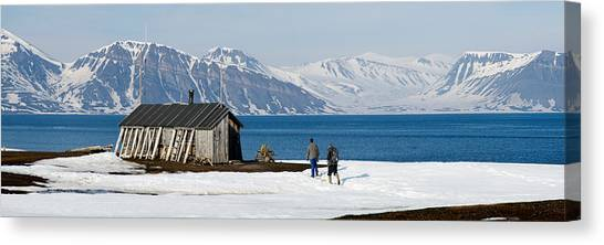 Log Cabin Canvas Print - Two Hikers Standing On The Beach by Panoramic Images