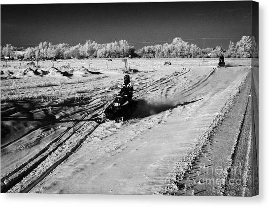 Harsh Conditions Canvas Print - two men on snowmobiles crossing frozen fields in rural Forget Saskatchewan Canada by Joe Fox