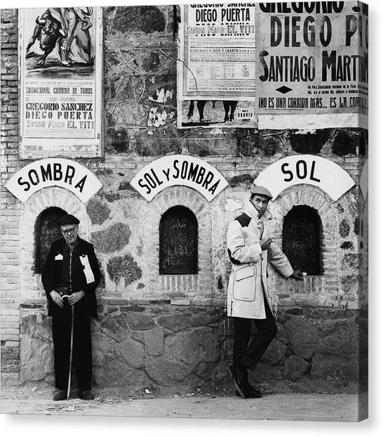 Two Men Posing By A Wall Covered In Spanish Canvas Print by Chadwick Hall