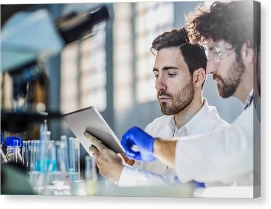 Two Scientist Using Digital Tablet In Laboratory Canvas Print by Poba