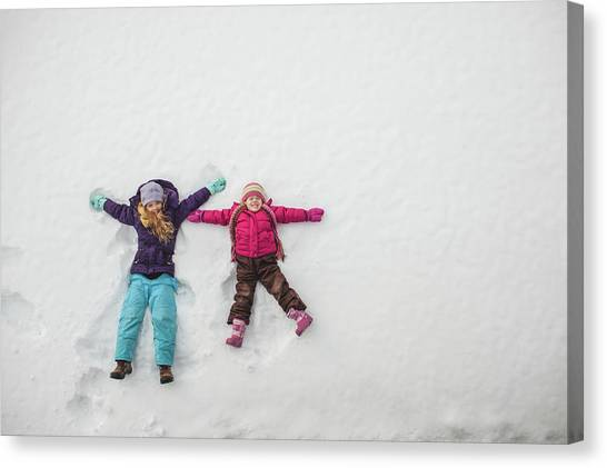 Two Sisters Playing, Making Snow Angels Canvas Print by Hugh Whitaker