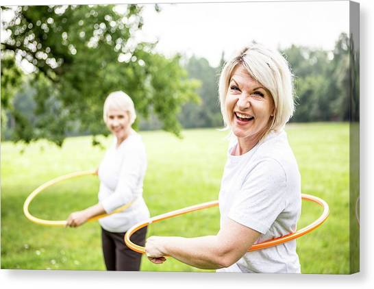 Two Women With Plastic Hoops Canvas Print by Science Photo Library