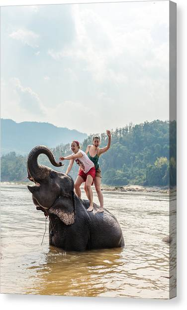 Two Young Women Riding An Elephant In The Mekong Canvas Print by Matteo Colombo