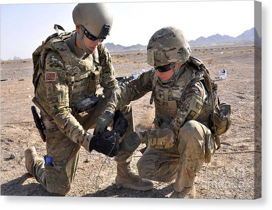 Nato Canvas Print - U.s. Soldiers Use Tape To Wrap by Stocktrek Images