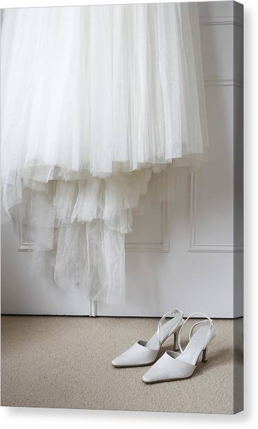 White Shoes On Floor Beneath Wedding Dress Hanging Outside Wardrobe Canvas Print by Michael Blann