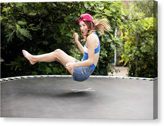 Trampoline Canvas Print - Woman Bouncing On Trampoline by Science Photo Library
