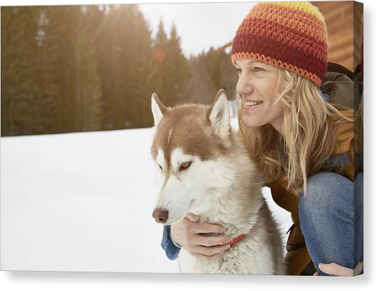 Woman Kneeling With Husky In Snow Covered Landscape, Elmau, Bavaria, Germany Canvas Print by Stephen Lux