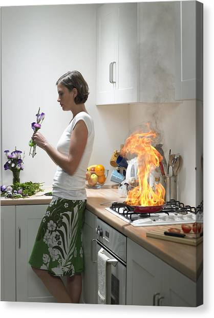 woman Leaning Against Kitchen Worktop Holding Flower, Frying Pan On Fire Behind Canvas Print by Michael Blann