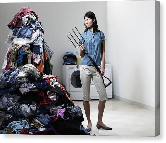 Woman Next To Pile Of Laudry With Pitchfork. Canvas Print by Ryan McVay