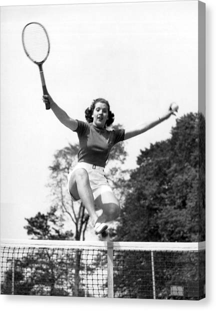 Tennis Racquet Canvas Print - Woman Player Leaping Over Net by Underwood Archives