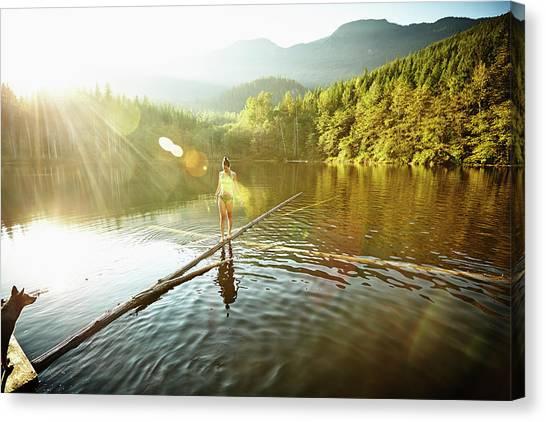 Woman Walking On Log In Alpine  Lake Canvas Print by Thomas Barwick