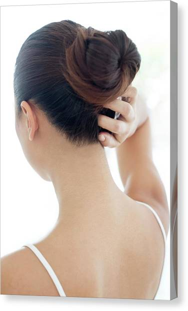Woman With Hair Bun Scratching Head Canvas Print by Science Photo Library