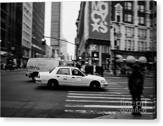 Manhatan Canvas Print - yellow cab taxi blurs past pedestrian waiting at crosswalk on Broadway outside macys new york usa by Joe Fox