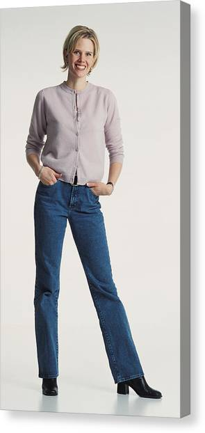 Young Beautiful Caucasion Adult Female Dressed Casually In Jeans And A Sweater Stands Smiling Confidently At The Camera Canvas Print by Photodisc