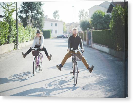 Young Couple Cycling With Legs Out Canvas Print by Eugenio Marongiu