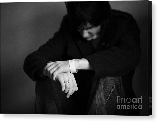 Young Dark Haired Teenage Man Sitting On The Floor With Back Against The Wall In The Fetal Position  Canvas Print by Joe Fox