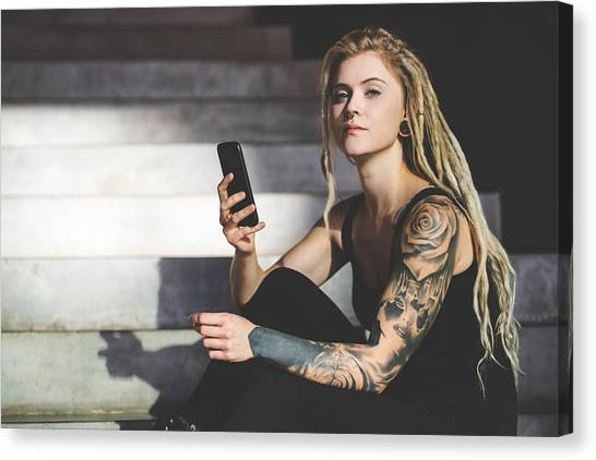 Young Tattooed Woman Texting Message On Mobile Phone Canvas Print by Nikada