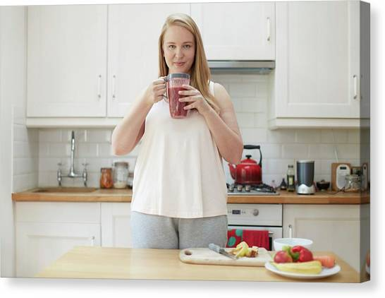 Smoothie Canvas Print - Young Woman Drinking Smoothie In Kitchen by Science Photo Library