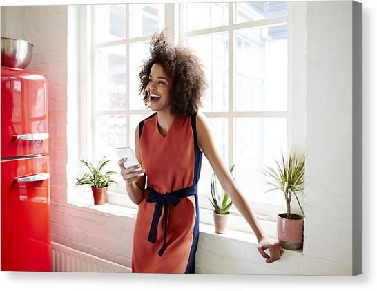 Young Woman Laughing In A Trendy Apartment Canvas Print by Ezra Bailey