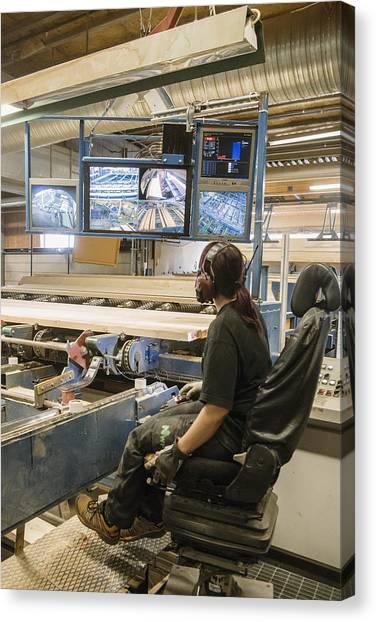 Young Woman Using Control Panel While Monitoring Computer Screens At Sawmill Canvas Print by Hakan Jansson