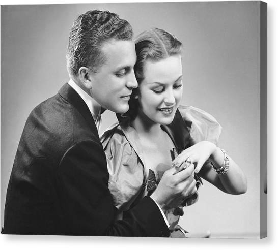 Man Putting Ring On Woman's Finger Canvas Print by George Marks