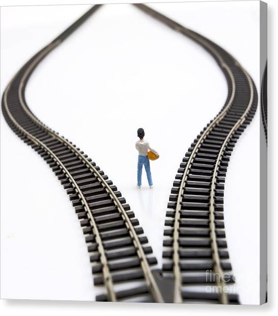 Cutout Canvas Print - Figurine Between Two Tracks Leading Into Different Directions Symbolic Image For Making Decisions. by Bernard Jaubert