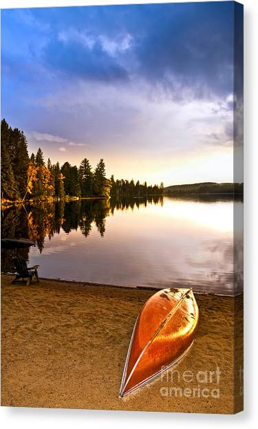 Lake Sunsets Canvas Print - Lake Sunset With Canoe On Beach by Elena Elisseeva