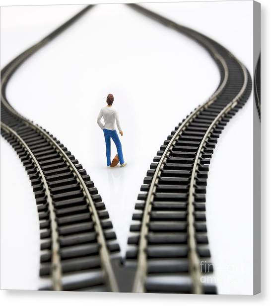 One Direction Canvas Print - Figurine Between Two Tracks Leading Into Different Directions Symbolic Image For Making Decisions. by Bernard Jaubert