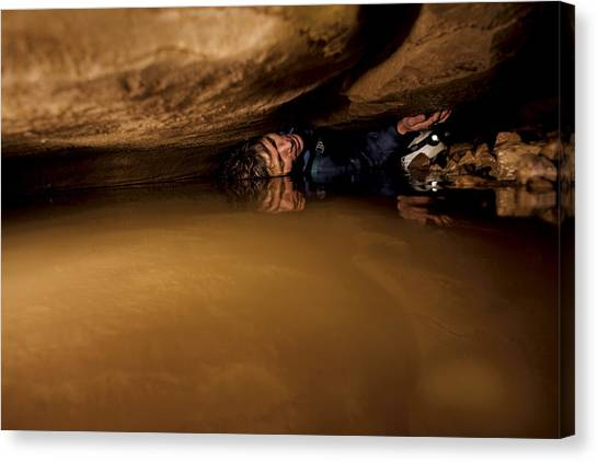 Spelunking Canvas Print - A Caver Moving In A Tight Space by Stephen Alvarez