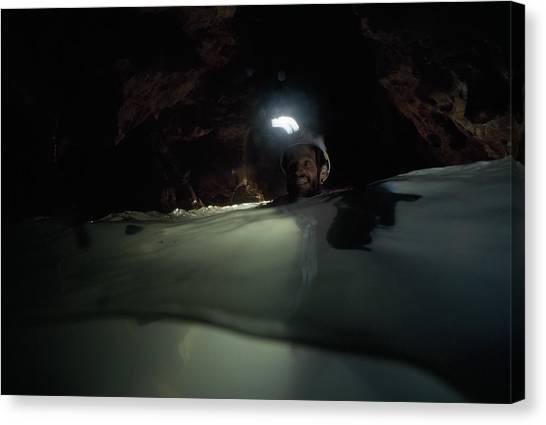 Spelunking Canvas Print - A Caver Swims Through An Underground by Stephen Alvarez